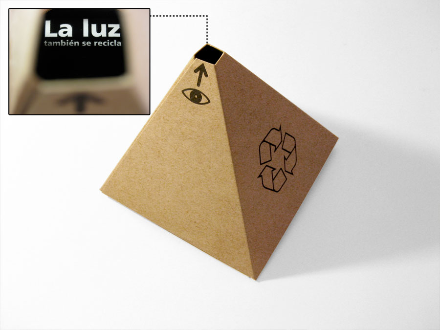 """The eye symbol invite to see through the hole. You can see a message (printed with reflective ink): """"La luz también se recicla"""" (Light also can be recycled)."""